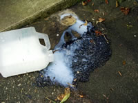 dropped pesticide container leaking into drain