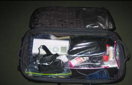 Suitcase with personal items in plastic bags